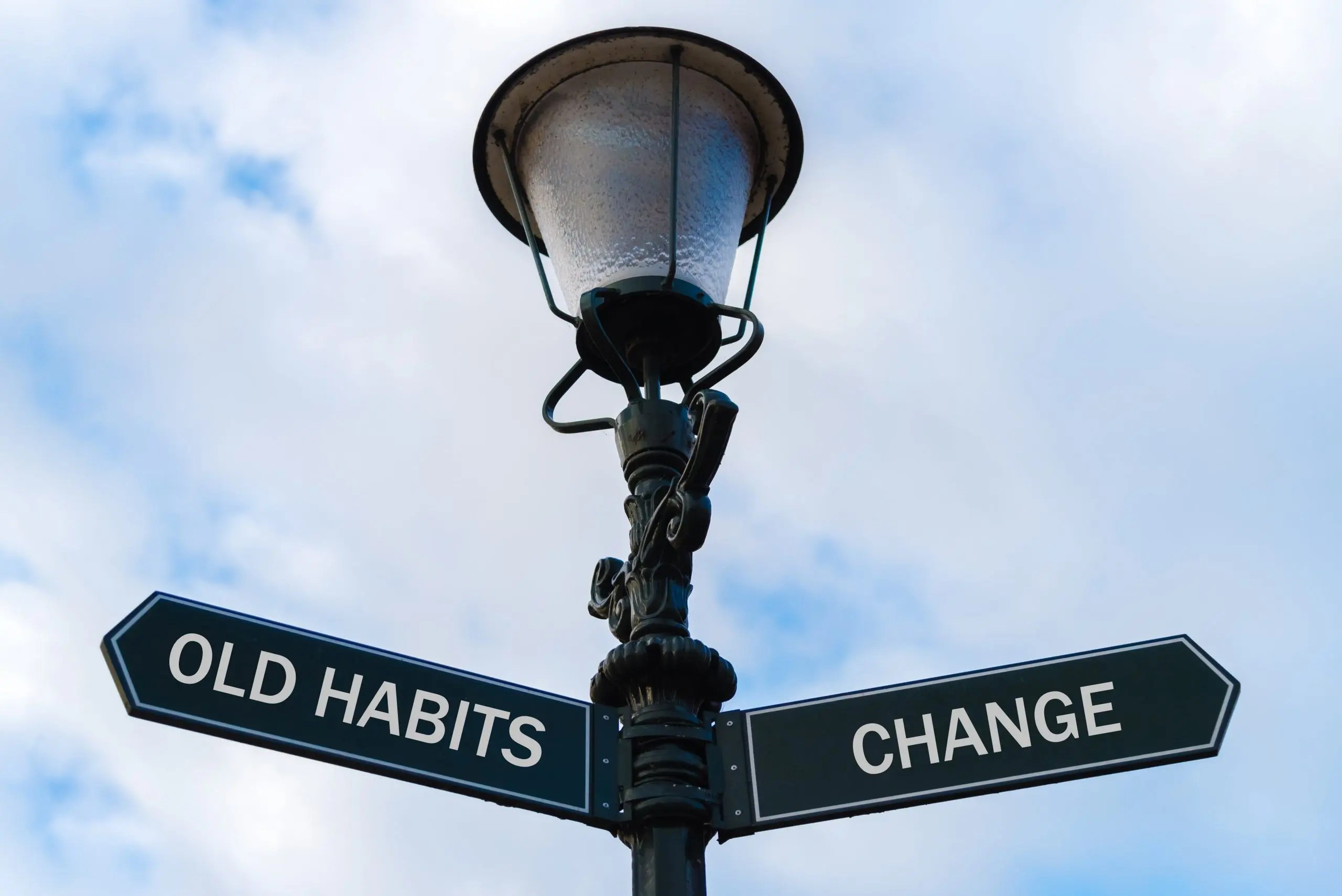 Old Habits versus Change directional signs on guidepost
