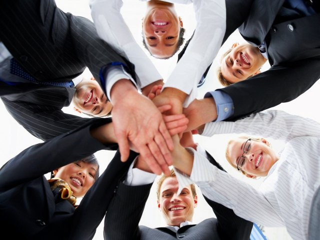 Six people standing in a circle with their hands on top of each other