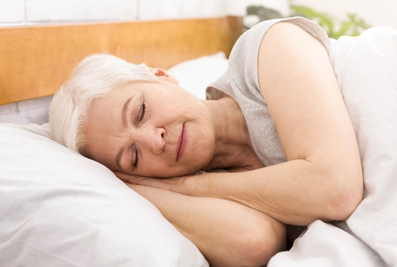 Older woman sleeping in bed. pear shaped body fat loss tips