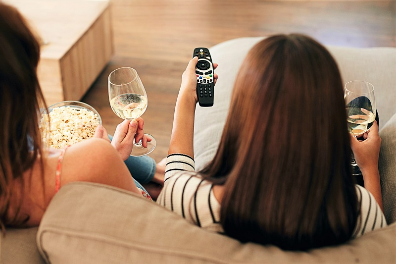 Two women having popcorn and wine in the evening