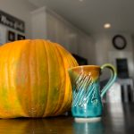 Orange pumpkins and mugs of tea.