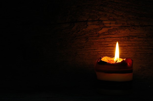 A candle lit against a wood wall.