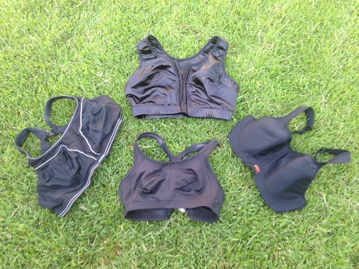 Four black running bras arranged on grass.