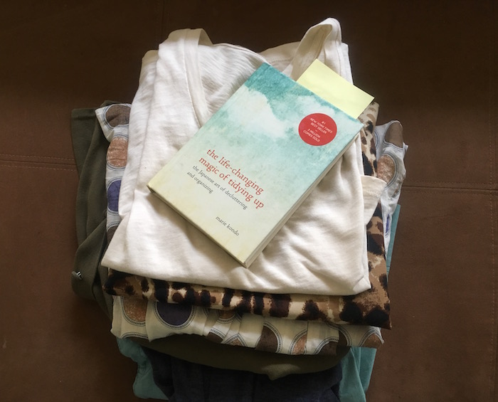 Photo of stack of folded clothes with Marie Kondo book on top.