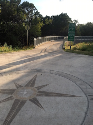 A compass in concrete marks the start of the urban cycling trail in Walnut Creek Park.