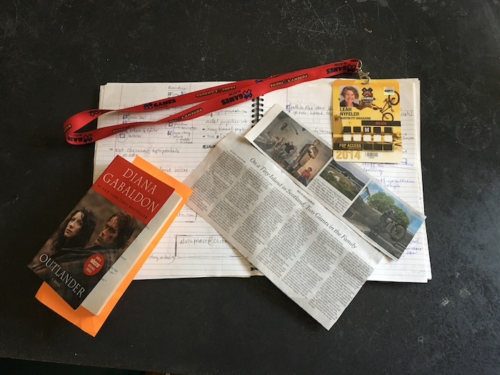 X Games press pass, copy of Outlander, New York Times article, and notebook are connected.