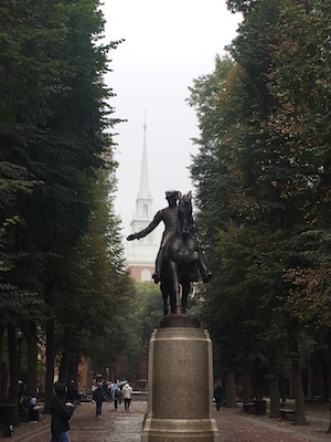 Famous Boston statue of Paul Revere on his horse with Old North Church Steeple in the background