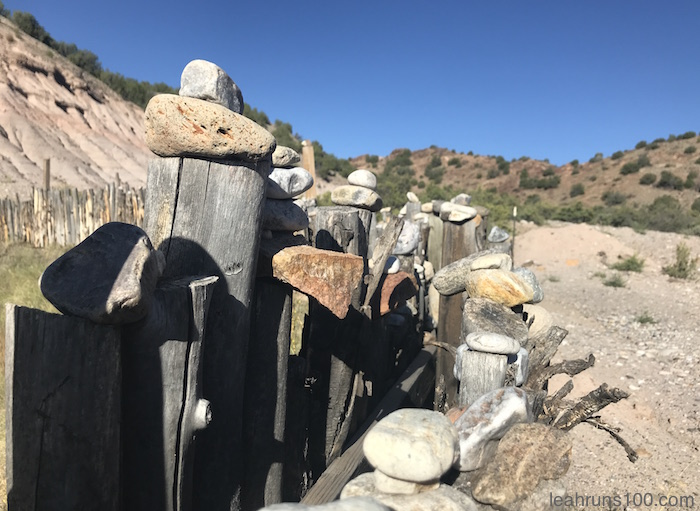 Stones on top of wooden fence at Ojo Caliente in New Mexico