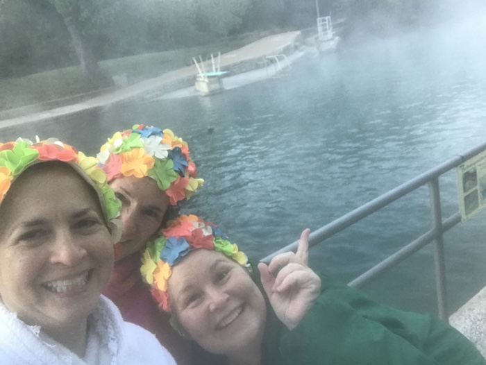 Three women in retro flower caps at Austin's Barton Springs pool, pointing out the mist