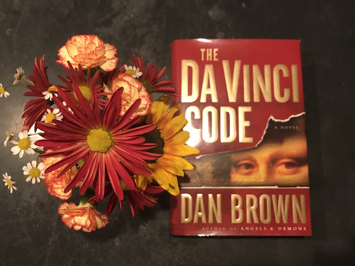 Cover of Dan Brown book, The DaVinci Code, with Thanksgiving flowers