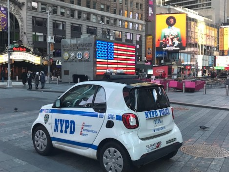 Times Square in NYC with American flag neon sign and NYPD car