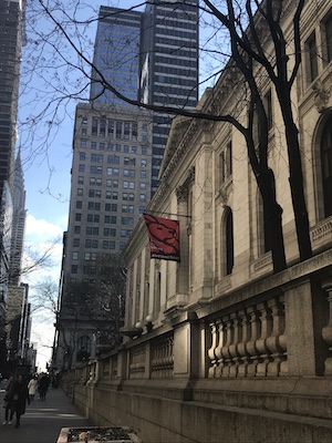 view down 42nd Street of New York City Public Library with library logo flag