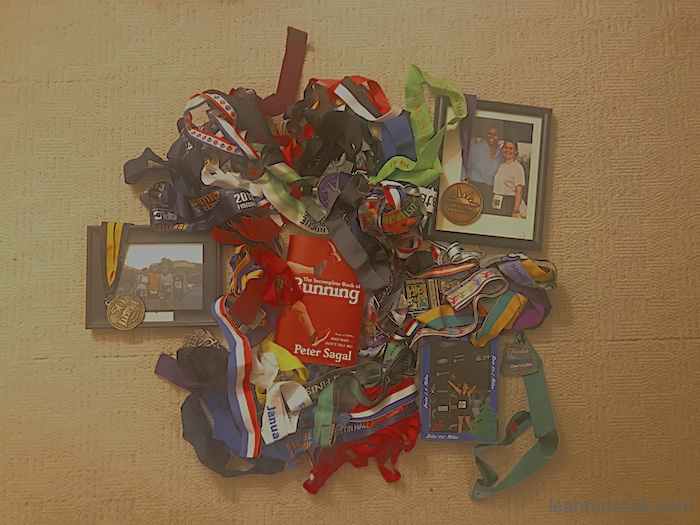 The Incomplete Book of Running by Peter Sagal surrounded by Leah Fisher Nyfeler's running medals and photographs