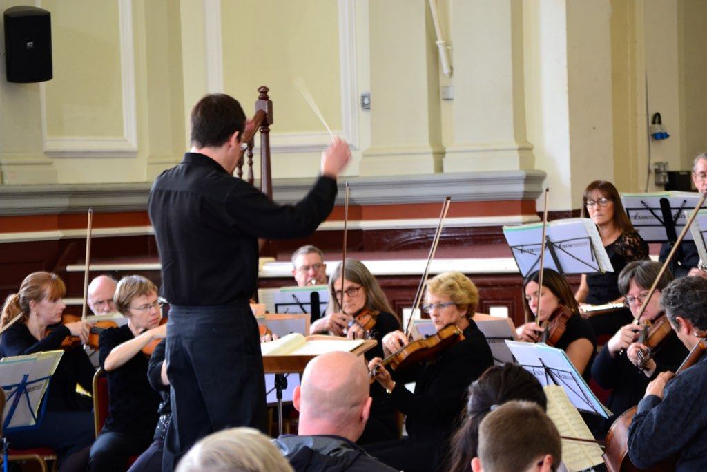Orchestral string players with conductor