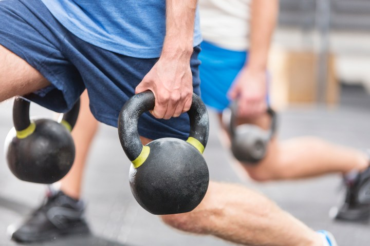 Cropped image of men lifting kettlebells at crossfit gym.jpg