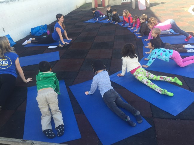 Happy Kid Yoga class with students in cobra pose