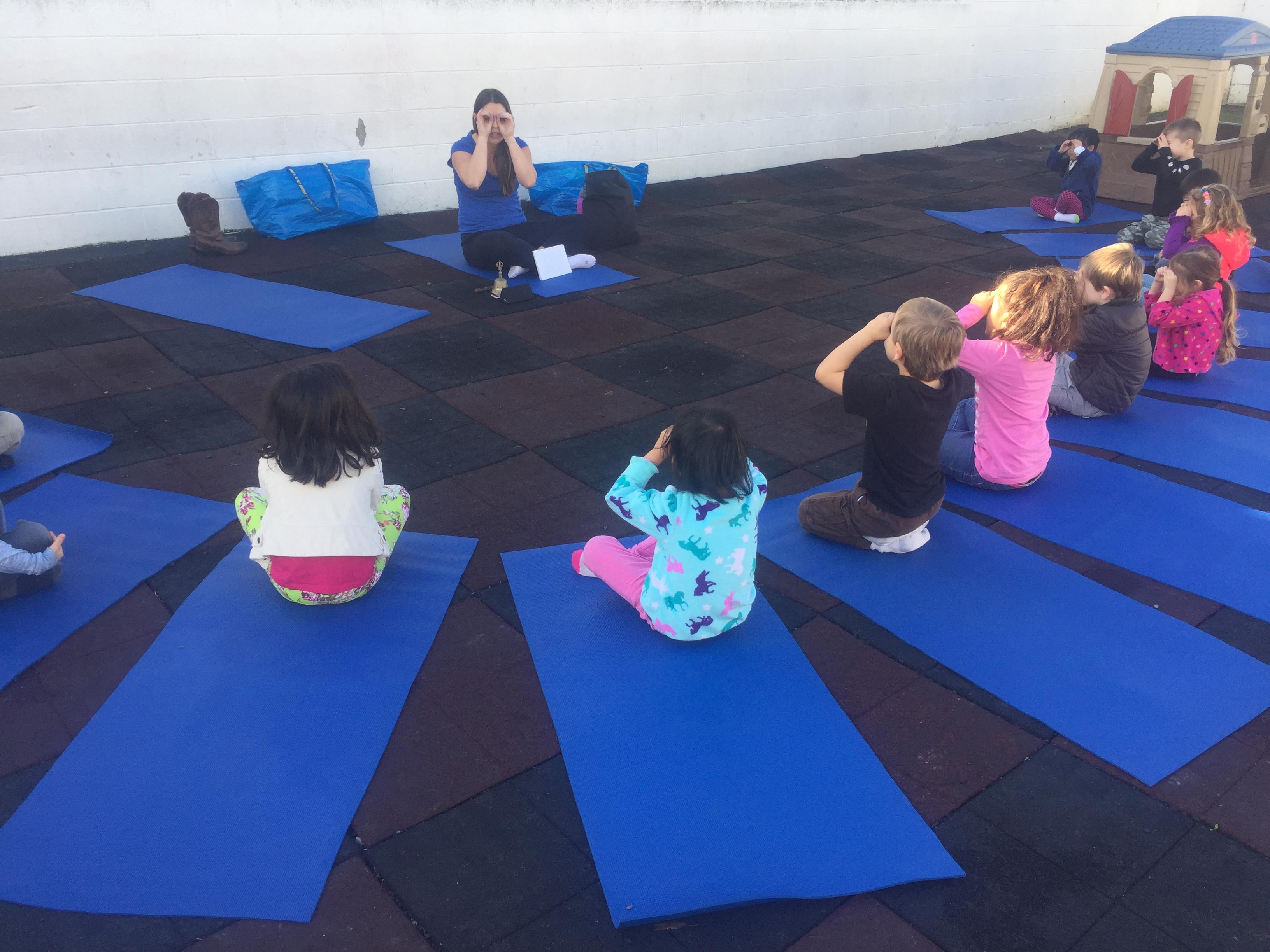 Happy Kid Yoga class pantomiming binoculars