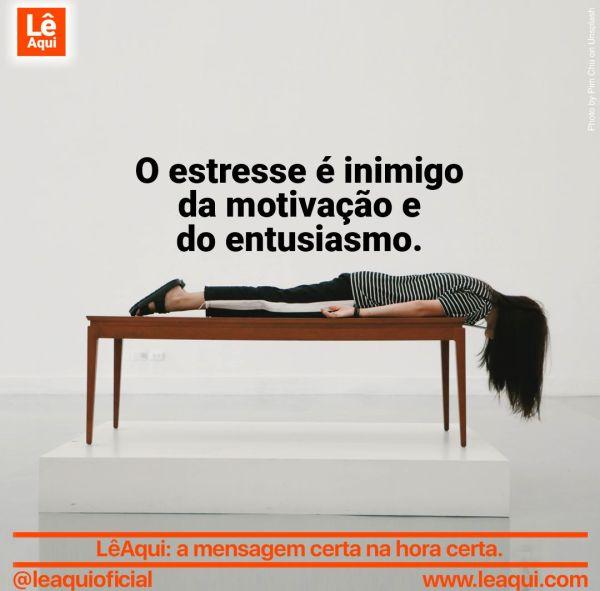 Mulher deitada de bruços em cima de uma mesa, com a cabeça pendente para fora por causa do estresse que é inimigo da motivação.