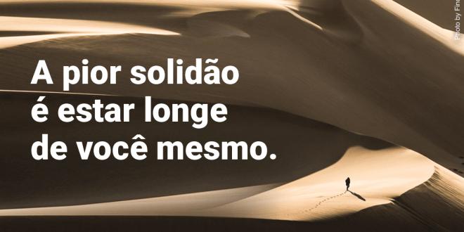 Solidão de uma pessoa que caminha sozinha por extensas dunas de areia.