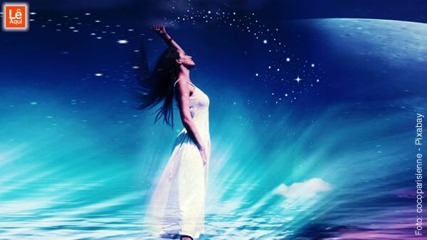 Mulher com braço ao alto e cabeça erguida, de olhos fechados, sob a luz das estrelas, para limpar a energia negativa