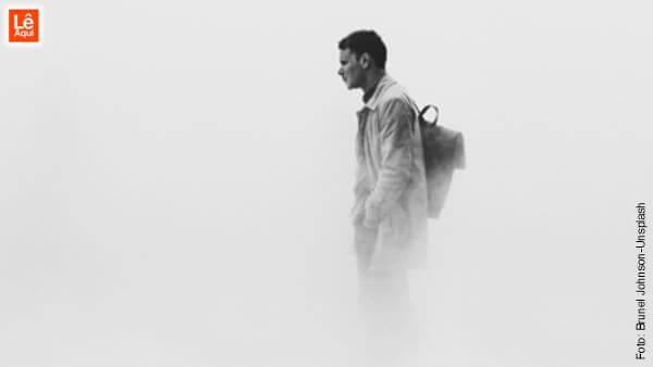 Homem andando com mãos no bolso, cabisbaixo, sob uma densa névoa. Dalai Lama explica como superar a depressão.