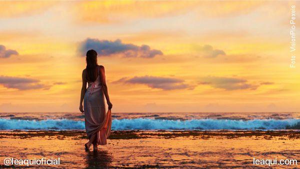 Mulher caminhando na beira de uma praia ao entardecer, simbolizando como é viver em paz