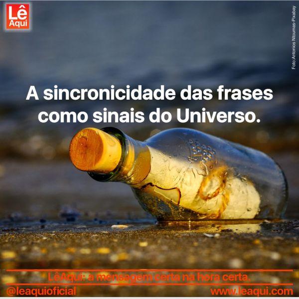 """Sobre as areias de uma praia, uma garrafa de vido com tampa de rolha e um papel enrolado dentro dela e a inscrição """"A sincronicidade das frases como sinais do Universo"""""""
