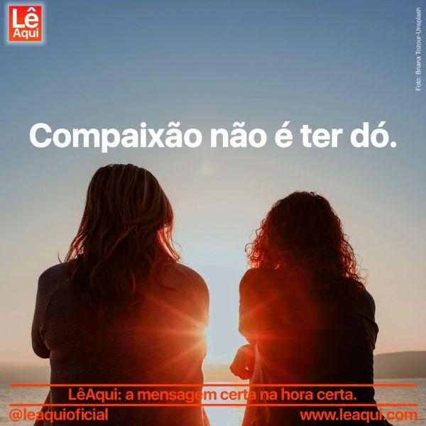 """Duas mulheres de costas sentadas lado a lado olhando o por do sol entre as montanhas e a inscrição """"Compaixão não é ter dó"""""""