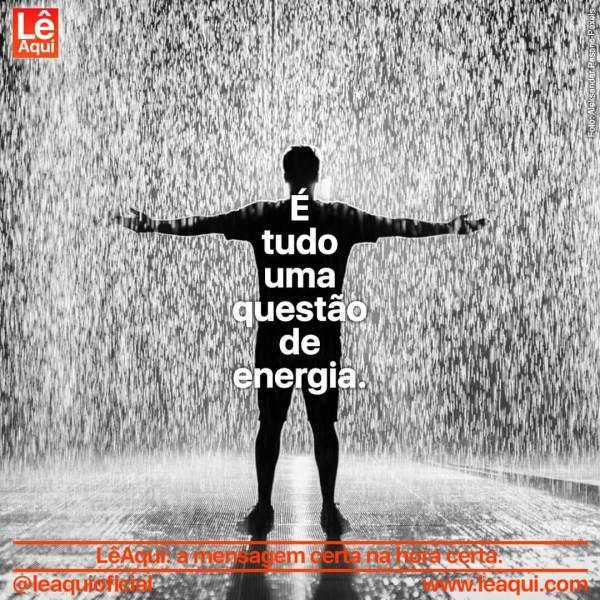 Homem de pé com os braços aberto sob forte chuva, indicando que tudo é questão de energia.