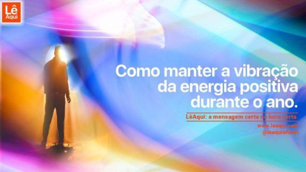 silhueta de homem sob fachos de luzes coloridas com a inscrição como manter a vibração da energia positiva durante o ano