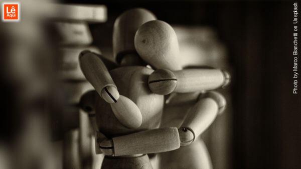Dois bonecos de madeira se abraçando - desapegue se a relação é fria e insensível.