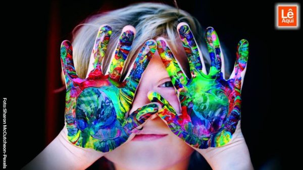 Criança com as mão pintadas na frente do rosto mostrando ser feliz