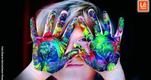 Criança com as mão pintadas na frente do rosto feliz
