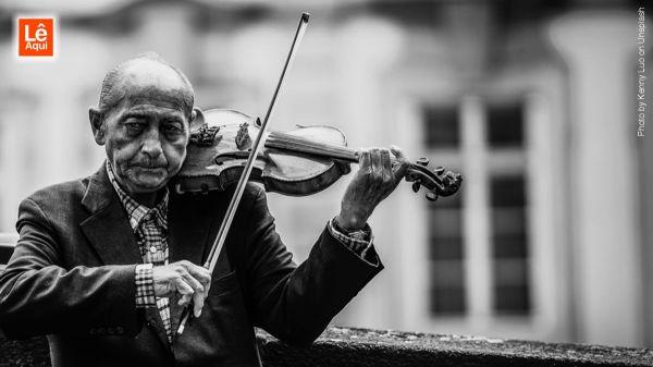 Senhor idoso tocando violino indicando a boa relação de música e alzheimer