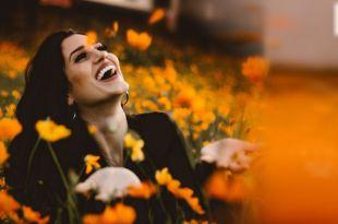 Jovem mulher em campo florido sorrindo sentindo a energia positiva
