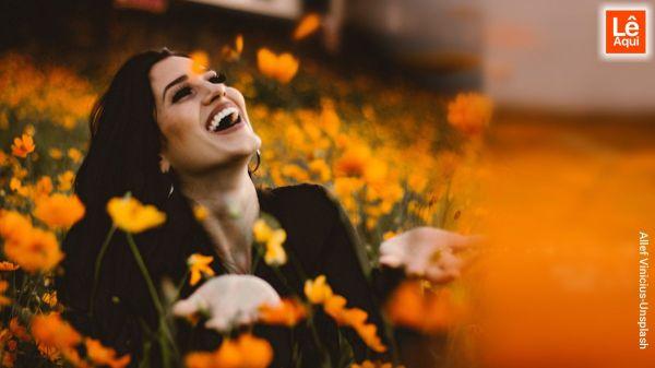 Jovem mulher em campo florido sorrindo sentindo a energia pura e positiva