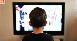 Menino assistindo televisão e assim o karma nasce na mente.