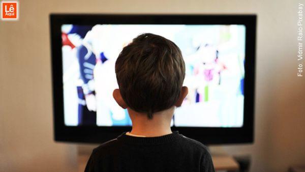 Menino parado em frente a uma televisão ligada, indicando que o karma nasce na sua mente.