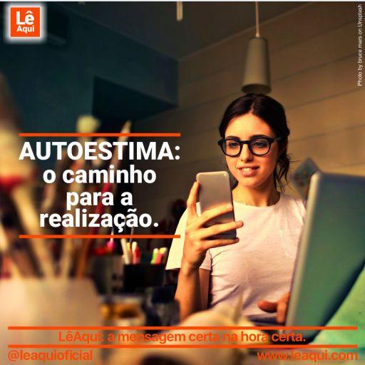 Moça sorrindo em frente a computador, com celular na mão e vários potes com canetas, lápis e pincéis mostrando que autoestima traz realização