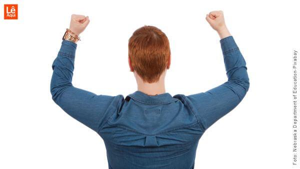 Homem com os braços levantados mostrando como se tornar um vencedor