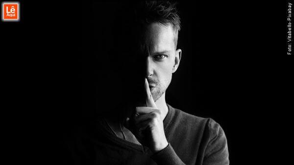 Homem com olhar arrogante com o dedo indicador na boca exigindo silêncio demonstrando a face sombria da autoestima