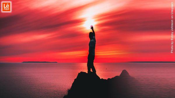 homem no alto de uma montanha com a mão direita erguida fazendo uma oração