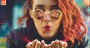 Moça ruiva com óculos escuros soprando purpurina rosa mostrando estar em paz