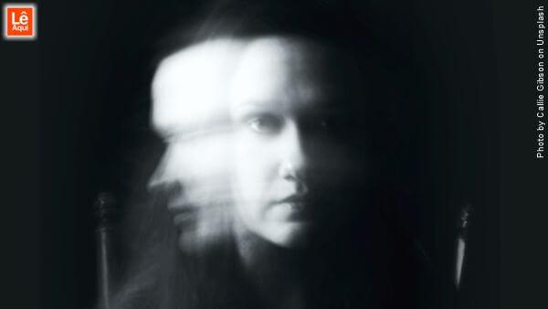Mulher no escuro sob influência de obsessor
