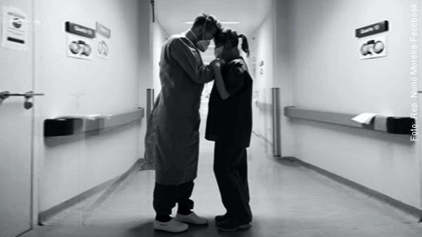 dois profissionais da saúde paramentados com roupas de proteção contra vírus consolando-se mutuamente mostrando que o amor é o antídoto para todos os males