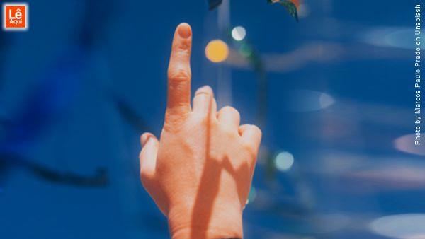 Mão com o dedo indicador apontando para o céu transmitindo mensagens de fé e esperança