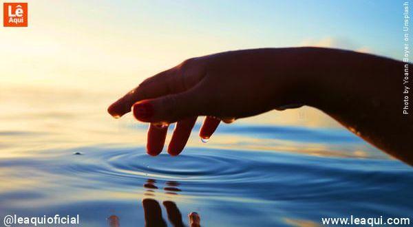 Mão feminina suavemente toca a superfície de um lago para equilibrar energia emocional
