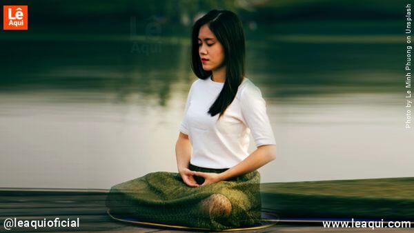 Moça sentada na posição e lótus meditando buscando através da respiração serenidade