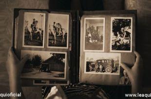 Mão segurando um antigo album de fotografias representando arrependimento