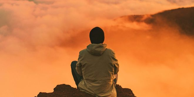 Homem sentado no alto de uma montanha observando o dourado horizonte com pensamentos manter boas vibrações
